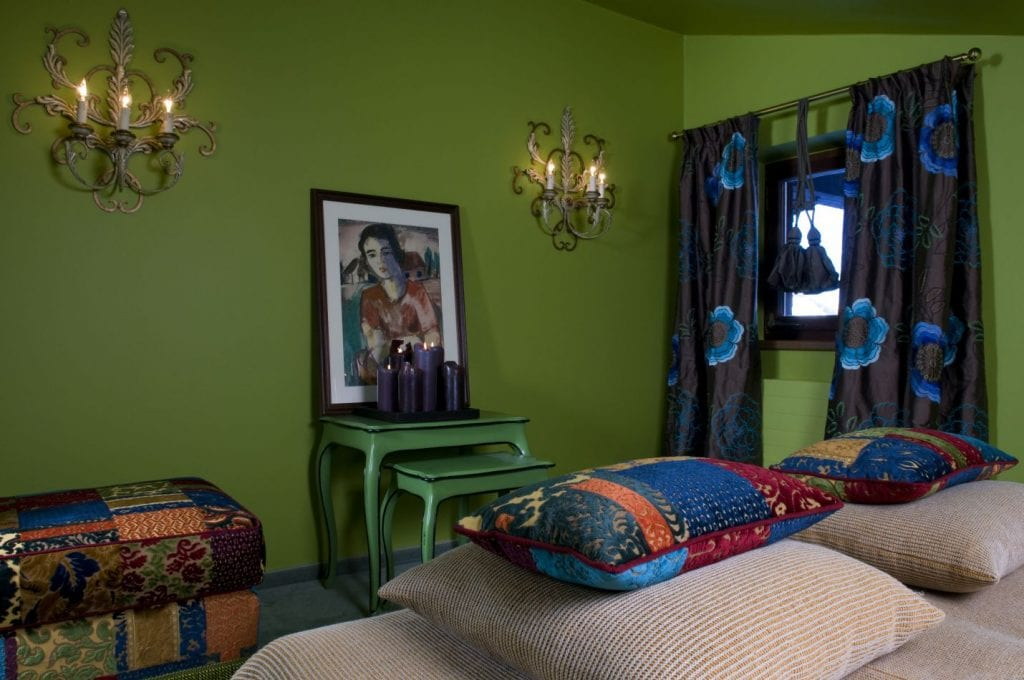 Quirky bedroom with green walls and bright textiles