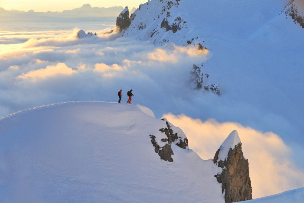 Panoramic view of mountain top with two skiers in Lech, Austria
