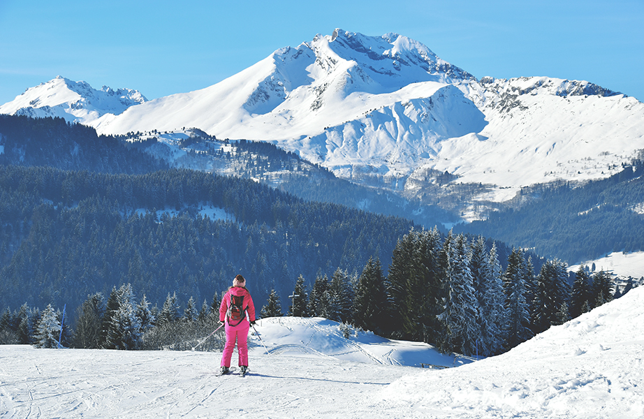 Blue skies over a mountain piste with a skier in a pink onesie.