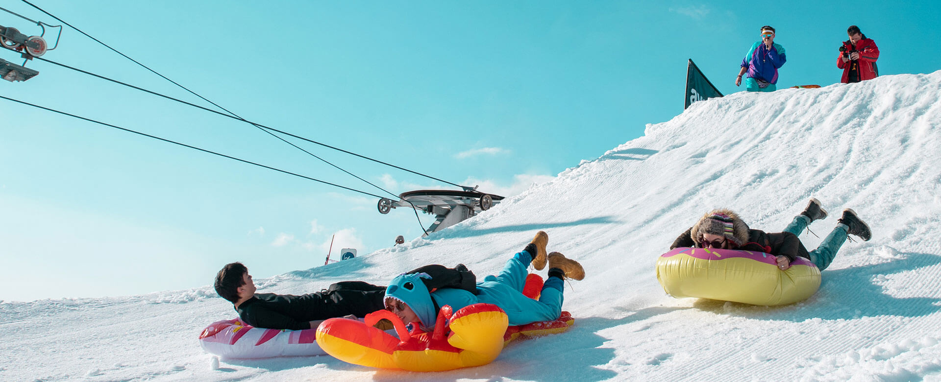 People racing downhill on inflatables in the shape of doughnuts and lobsters in the snow at Snowboxx festival