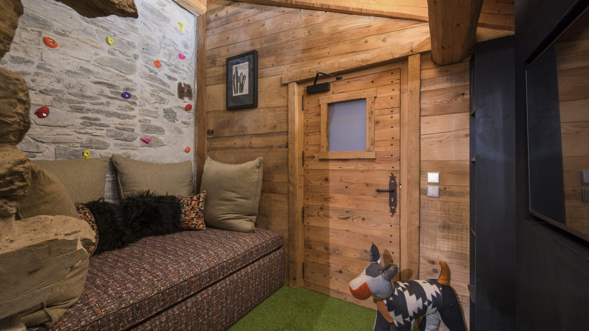 Chalet du Cret play room with fake grass and rock climbing wall for kids