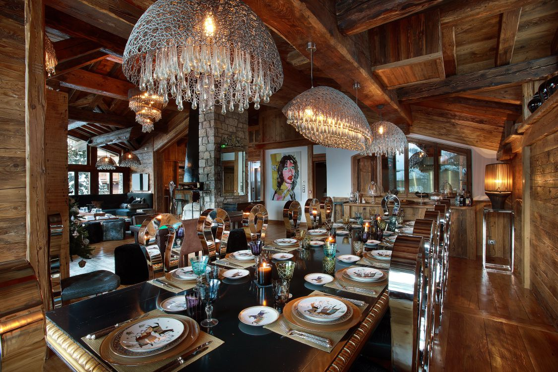 Chalet Marco Polo dining room area with lavish chandeliers, table set and Mick Jagger artwork in the background.