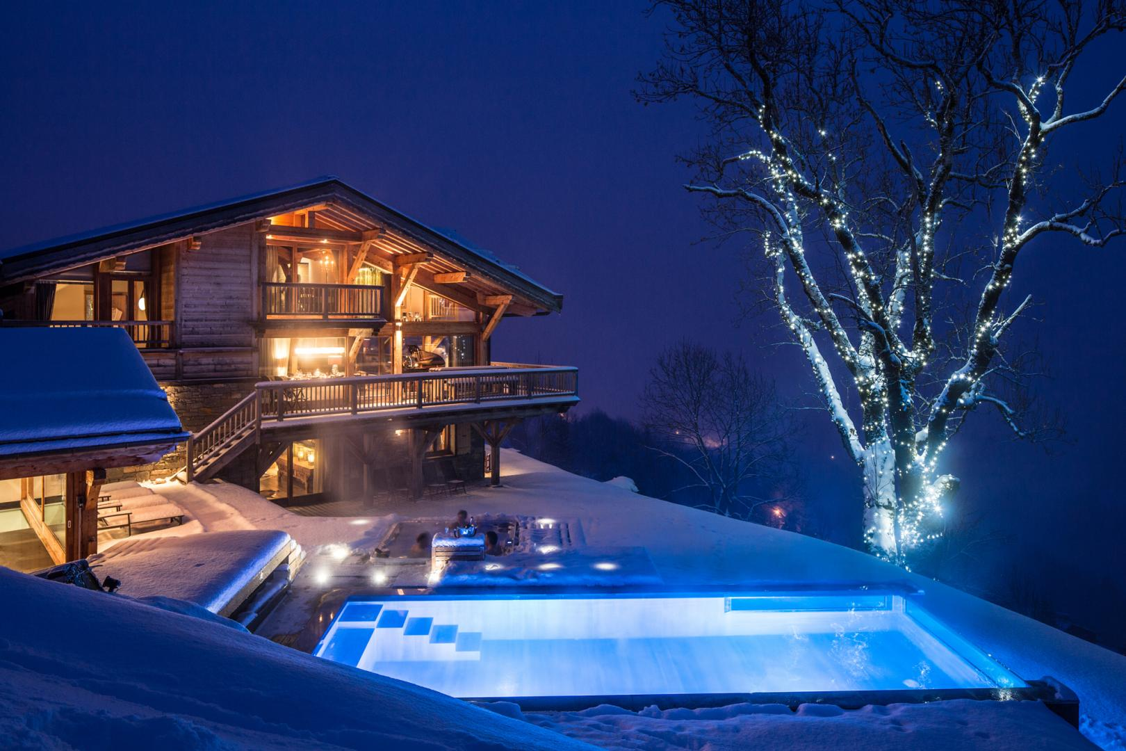 Chalet Grande Corniche outdoor are showing swimming pool and hot tub lit up at night.