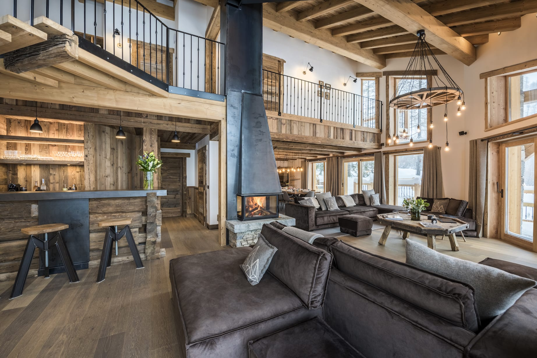 Chalet Machapuchare living room with mezzanine, fireplace, kitchen stools and comfy grey sofas.