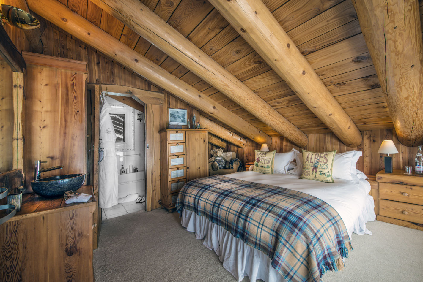 Chalet Le Chardon master bedroom with large wooden beamed celining.